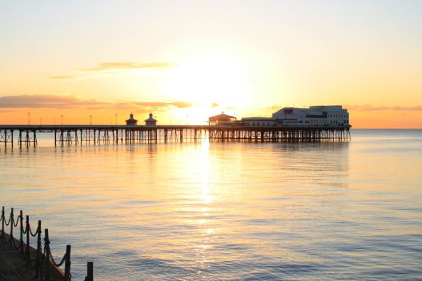 The Sun sets into the sea behind North Pier