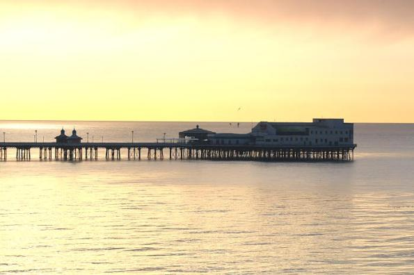 Alow sun behind North Pier anda snow filled sky.